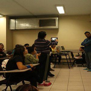 Sala de clases en la cual un alumno está de pie grabando con su tablet a su profesor