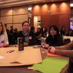Asistentes sentados en mesas redondas de la inauguración.
