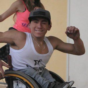 Se ve a un joven de 19 años mirando hacia la cámara en una silla de ruedas.
