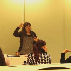 Se ve a una profesora realizando lengua de señas y a una alumna imitándola