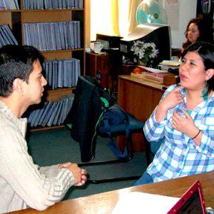 Se ve a dos personas comunicándose con lengua de señas