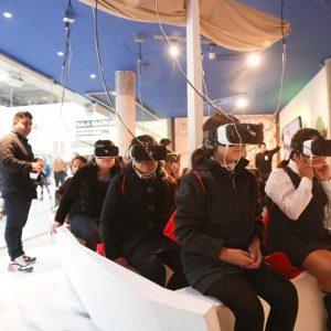 Niños vestidos de uniforme, sentados sobre un bote ficticio, usando lentes de realidad virtual