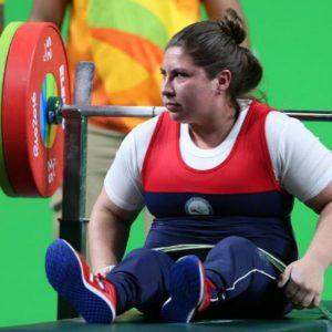 La levantadora de pesas María Antonieta Ortiz se encuentra concentrada y sentada con las pesas de fondo a la espera de su participación en Río 2016